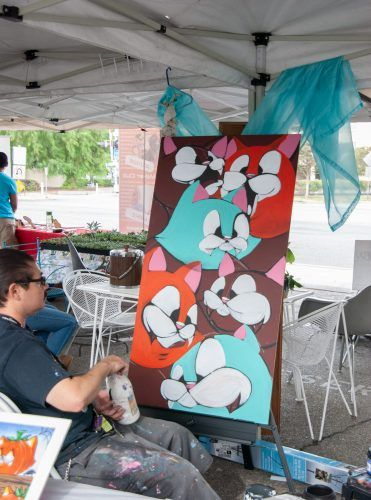 Joe Ded, a freelance artist from Montclair, puts the finishing touches on a piece for a cat community shelter Sunday at the Claremont South Village Block Party. / photo by Eric Rangel