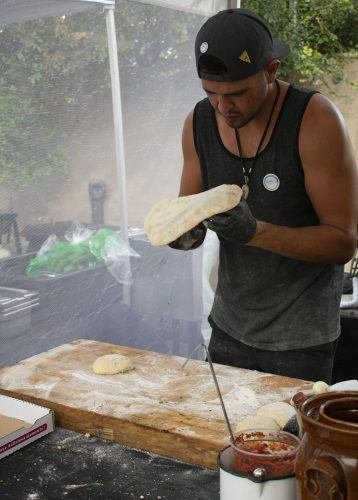 Justin Amaro, owner of An Amaro Pizzeria, a vegan pizza company, kneads dough at the Old Stump Brewery Vegan Kickback in Pomona Sunday. Other vendors served vegan sushi and tacos. / photo by Maydeen Merino
