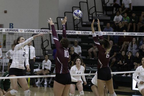 Leopard freshman right side hitter Ayana Mier spikes the ball over Bulldogs middle blocker Hannah Lanyon and outside hitter Christina Casey. The Leopards swept the Bulldogs 3-0 and improve to 2-1 in conference. They return to host Cal Lutheran Saturday at 4 p.m. / photo by Melody Blazauskas