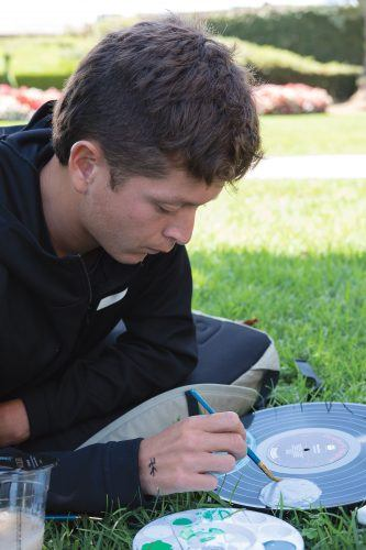 Joey Reyes, sophomore criminology major, paints the solar system on a vinyl record at the Campus Activities Board's Sip and Paint event at the University Quad Monday. / photo by Nathan Hua