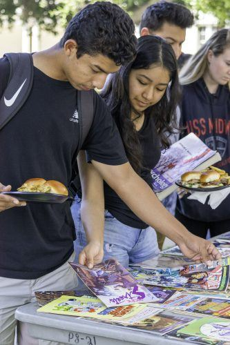 Freshman kinesiology major Michael Hernandez Jr. and freshman psychology major Sherly Aviles-Morgado browse the selections Wednesday at the Campus Activities Board's National Comic Book Day celebration in Sneaky Park. Students were allowed to take two free comic books. / photo by Veronyca Norcia