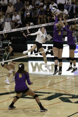 Regal sophomores, middle blocker Maci Haddad and outisde hitter Madison Karcich, go up to block a spike from Leopard sophomore outside hitter Hayley Celaya in La Verne's game against Cal Lutheran Sept. 28. The Leopards took the match 3-1 and improved to 4-1 in SCIAC. / photo by Melody Blazauskas