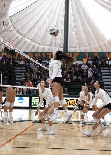 Pi'ikea Clemens, junior outside hitter for the Leopards, spikes the ball over Whittier senior middle blocker Valerie Van Der Linden and sophomore setter Makayla Wright in La Verne's game against the Whittier Poets Saturday. The Leopards lost the game, 3-2. / photo by Nathan Hua