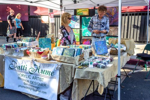 Patti Hume, an acrylic artist, and her husband, Peter Hume, sold acrylic paintings on different sized canvases on Saturday at the 38th annual Village Venture. Several other artists also attended the Village Venture, each displaying and selling their art./ photo by Veronyca Norcia