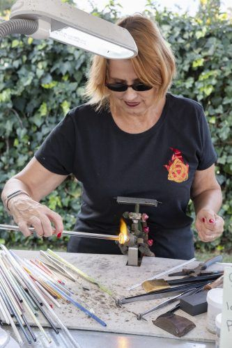 Mary Swartzel, a resident of Riverside, flame-works glass art Saturday at the Handmade Craft Fair at the St. Peter the Apostle Orthodox Church in Pomona. / photo by Nathan Hua