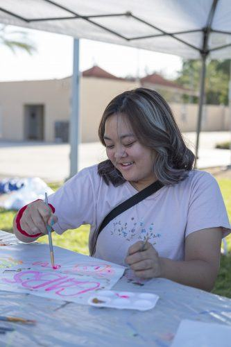 Gabby Balais, a resident of Chino Hills, paints her kite at the Cal Poly Pomona Kite Festival hosted by Cal Poly's Swift Games Club on Nov. 8. Guests had the option to either bring their own kites, or decorate blank kites that were provided by the club. For those who were not flying kites, there were other activities such as interactive games to play while watching other kites take to the sky. / photo by Nathan Hua
