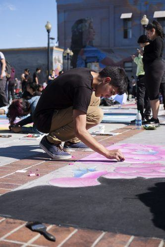 Alex Garcia, a resident of Freemont, draws flowers at the 13th Annual Chalk Art Festival in Pomona Saturday. The free event attracted over 300 participants. / photo by Nathan Hua