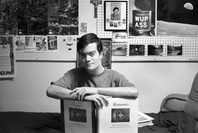 """Nathan Baca, a freshman broadcasting major, rests on his two written novels. Baca wrote his first novel, """"Westwinds"""" (right), while in high school. He is currently writing his second project, """"Aurora"""" (left). / photo by Juan Garcia"""