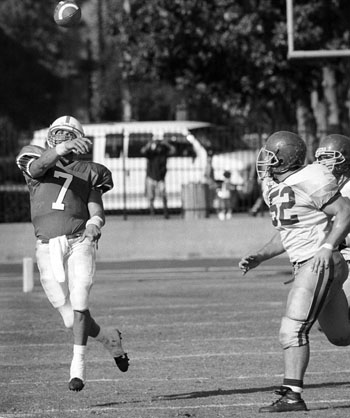 Senior quarterback Dan Blahy (#7) evades the attack on John Filson (#52) while throwing the ball down field. Blahy passed for two touchdowns for 250 yards and rushed for one touchdown. La Verne is now 3-0 in conference. / photo by Ian Gratz
