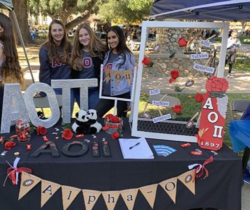 Kendall Ebert, senior educational studies major, Emily Gosdanian, sophomore communications major and officer for Alpha Omicron Pi, and Amber Kushwaha, sophomore business administration major, display a Rose Bowl themed booth for Alpha Omicron Pi at the club fair Feb. 5. / photo by Rashonda Taylor