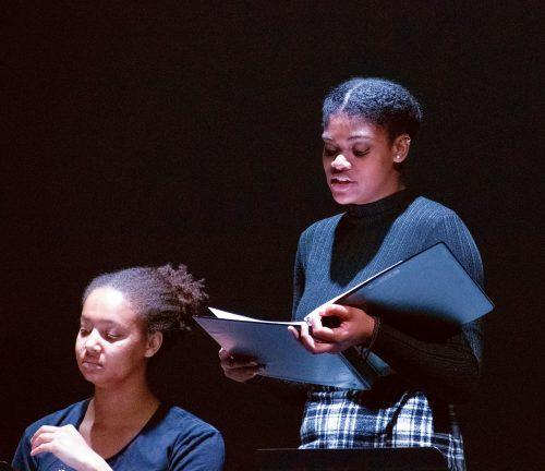 """Jasmine Scott, junior creative writing major, and Shy Glothon, junior theater arts and psychology major, perform in the staged reading of Toni Morrison's """"The Bluest Eye,"""" which focuses on the lack of media representation of African American women and how it affects their self-esteem. / photo by Liliana Castañeda"""