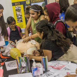 A student from Palomares Academy for Health Sciences booth shows children how to perform CPR on an dummy. The STEAM Fair is in partnership with Cal Poly Pomona in order to get kids interested in science, technology, engineering, arts and math.