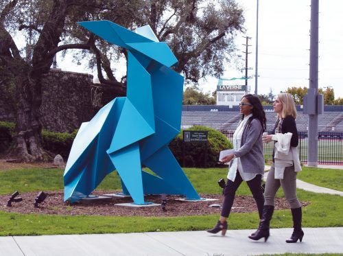 "Alexandra Burrel and Shannon Capaldi walk by the origami-inspired sculpture that is called ""Rabbit,Sitting"" and was created by Los Angeles based artist Hacer and is now permanently lodged at the University Quad, in front of Dailey Theatre. / photo by Liliana Castañeda"