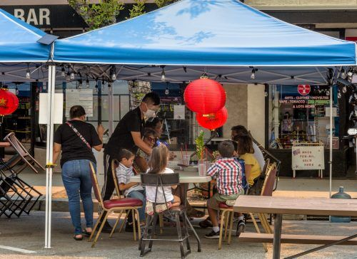 A family enjoys outdoor dining Wednesday at Cafe Wang on D Street in downtown La Verne, despite ashes flying from nearby fires in the San Gabriel mountains. In July the city of La Verne closed the street to make room for restaurants' increased outdoor dining options. / photo by Mya-Lin Lewis