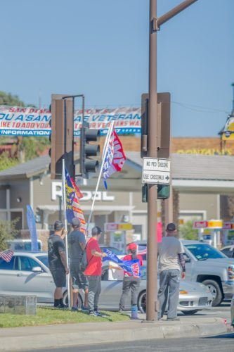 A small group of supporters of President Donald Trump wave their flags and banners on the corner of Bonita Avenue and Arrow Highway in San Dimas on Saturday. They gathered to express opposition to the Black Lives Matter protest in downtown La Verne that same day. / photo by Mya-Lin Lewis