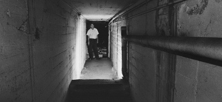 University of La Verne Safety Coordinator Jeff Boster stands at the south entrance of an old conveyor tunnel in the maintenance warehouse. The tunnel extends under First Street for more than 150 feet on the north side to the maintenance warehouse on the south side. The tunnel was used by the citrus packing industry when the building was a packing house. Today, the tunnel is blocked on the north end and lies unused. / photo by Ryan Sones