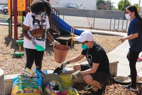 Juliana Pichay, right, justice resident for the Solid Rock Church, helps two volunteers fill their pots to start gardening on Saturday at aommunity garden event. The church, located at 1364 N. Towne Ave. in Claremont, is starting a community garden. / photo by Rachel Kendrick