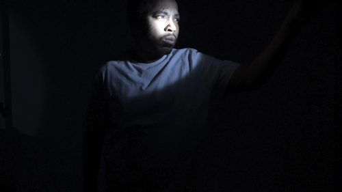 """D. Hill, adjunct professor of photography, spotlights himself in order to show the color of his skin in his visual art performance """"Remove the Noose by All Means Necessary,"""" for Muzeo on Saturday via Zoom. / photo courtesy of D. Hill"""