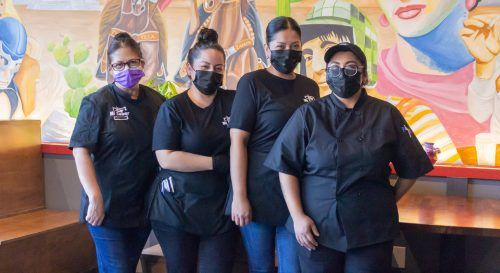 Mi Sabor Mexican Kitchen employees Kathy Hernandes, Sandy Magana, Sabina Magana, Angela Pena pose inside the restaurant, highlighting its traditional decor. Owner Sandy Magana opened Mi Sabor March 8 after a year of complications caused by the pandemic. / photo by Shira O'Neal-Abend