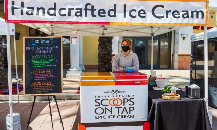 Scoops on Tap employee Deanna Swager welcomes customers at the Terra Vista Farmers Market in Rancho Cucamonga on April 17. The company makes a variety of artisanal ice cream flavors, including vegetarian and keto options. They can be ordered online for pick up at Scoops on Tap's Montclair warehouse, or at farmers markets throughout Southern California. / photo by Christine Diaz