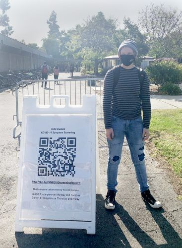 Claremont High School senior Kellin Olsen stands next to the code students must scan to fill out their COVID-19 symptom check form before entering campus. The Claremont Unified School District reopened for in-person instruction April 12. / photo by Alondra Campos