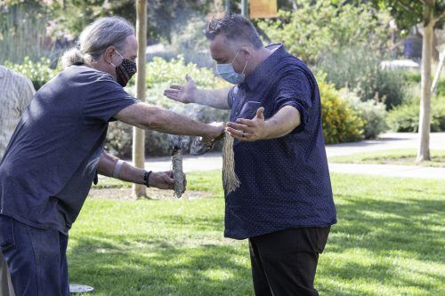 Dan Kennan, adjunct professor of sociology, cleanses Trevor Thomson, a member of the Karuk Tribe of California, with wing and sage in preparation for a sage blessing ceremony Sept. 10 at the Ludwick Center. The California White Sage used in the ceremony grows outside the Ludwick Center and is considered sacred by the local indigenous community. / photo by Darcelle Jones-Wesley