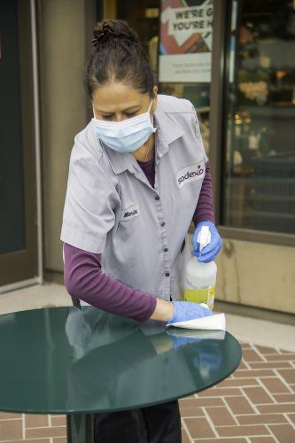 Maria Zavala of Sodexo housekeeping services cleans the tables outside the University Bookstore on Thursday. This disinfecting work is done regularly in an effort to contain the spread of the coronavirus throughout campus. / photo by Darcelle Jones-Wesley
